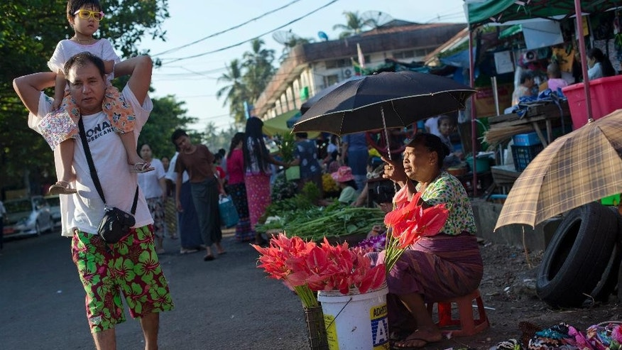 A man carries a child as a flower vendor watches in Yangon, Myanmar, Saturday, Nov. 7, 2015. On Sunday Myanmar will hold what is being viewed as the country's best chance for a free and credible election in a quarter of a century. (AP Photo/ Gemunu Amarasinghe)