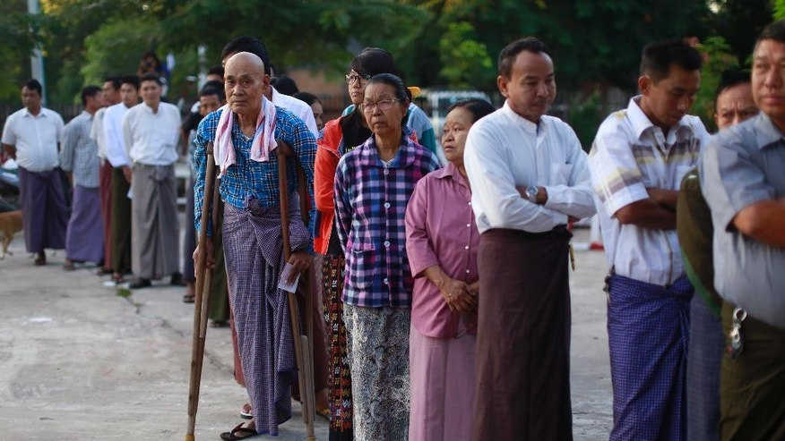 People stand outside a polling station in Mandalay, Myanmar, Sunday, Nov. 8, 2015. Myanmar voted Sunday in historic elections that will test whether popular mandate will help loosen the military's longstanding hold on power even if opposition leader Aung San Suu Kyi's party secures a widely-expected victory. (AP Photo/Hkun Lat)