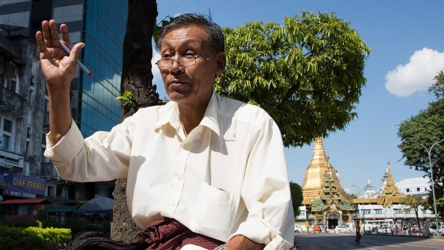 Fortune teller Saan Aung gestures as he predicts a win for the military-backed Union Solidarity and Development Party in Sunday's election, in Yangon, Myanmar, Saturday, Nov. 7, 2015. With an eye on Sunday's general elections, some street-side palm readers and astrologers are talking about the winds of change, others days of doom.   (AP Photo/Mark Baker)