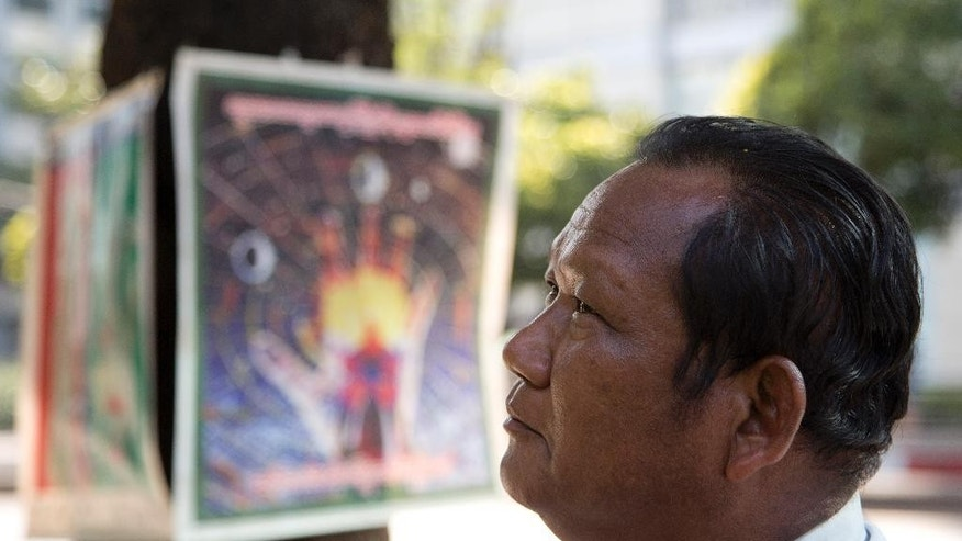 Fortune teller Kairo Thitsa predicts a win for the NLD party in Yangon, Myanmar, Saturday, Nov. 7, 2015. With an eye on Sunday's general elections, some street-side palm readers and astrologers are talking about the winds of change, others days of doom.   (AP Photo/Mark Baker)