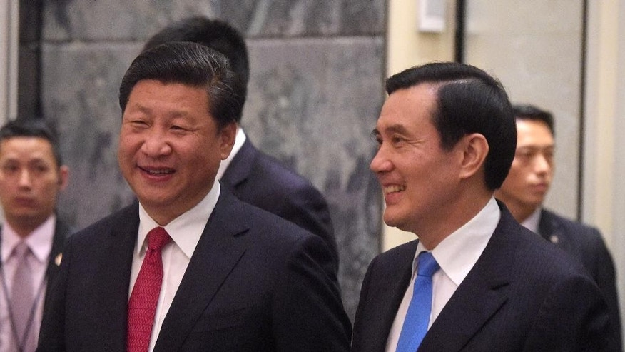 Chinese President Xi Jinping, left, and Taiwanese President Ma Ying-jeou, right, smile as they enter the room at the Shangri-la Hotel where they met on Saturday, Nov. 7, 2015, in Singapore. The two leaders shook hands at the start of a historic meeting, marking the first top level contact between the formerly bitter Cold War foes since they split amid civil war 66 years ago. (AP Photo/Joseph Nair, pool)