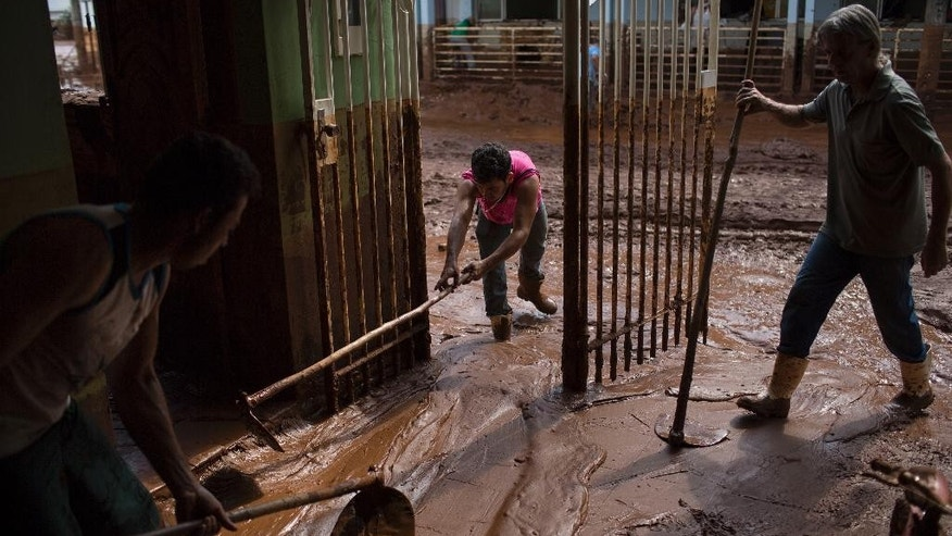 People remove mud from a damaged home in Barra Longa after a dam burst on Thursday in Minas Gerais state, Brazil, Saturday, Nov. 7, 2015. Brazilian searchers are looking for 23 people still listed as missing following the burst of two dams at an iron ore mine in a southeastern mountainous area. (AP Photo/Felipe Dana)