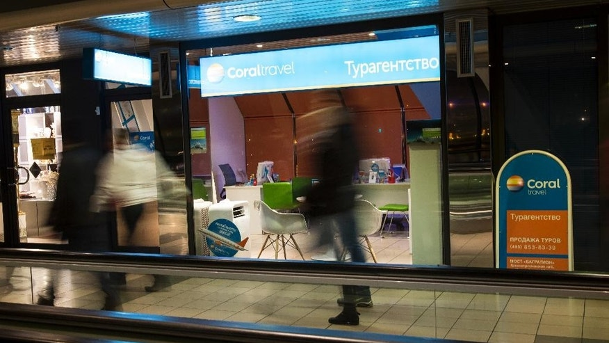 People walk by a window of a travel agency in Moscow, Russia, Friday, Nov. 6, 2015. Russian President Vladimir Putin agreed to suspend all Russian flights to Egypt on Friday after a recommendation by his chief of intelligence for a halt until the cause of last week's crash of a passenger jet in the Sinai Peninsula is determined, as an official said pieces of wreckage from the plane had been brought to Moscow to test for possible traces of explosives. (AP Photo/Alexander Zemlianichenko)