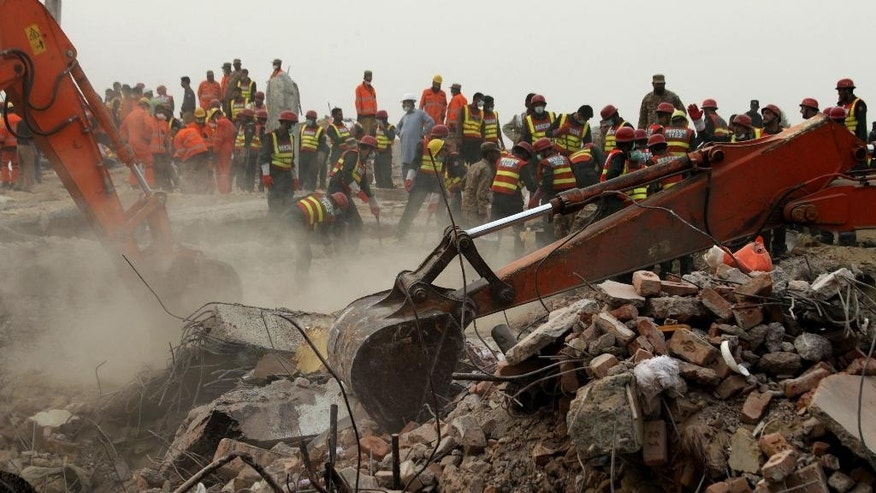 Excavators dig rubble of a collapsed building looking for survivors in Lahore, Pakistan, Friday, Nov. 6, 2015. A spokesman for a Pakistani rescue agency says hopes are starting to fade for finding more survivors in the rubble of a four-story factory which collapsed this week killings dozens of people left many injured. (AP Photo/K.M. Chaudary)