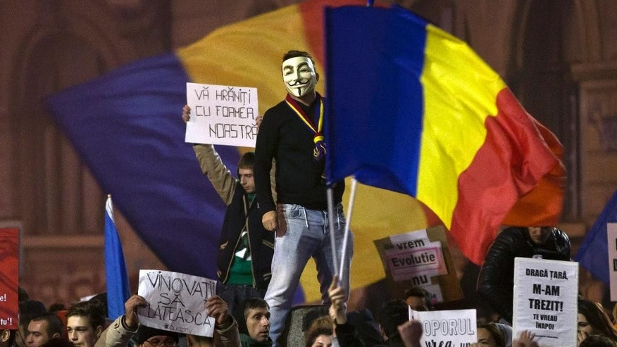 "A man wearing a Guy Fawkes mask stands above protesters shouting slogans against the Romanian politicians during the fourth day of protests, joined by tens of thousands across the country, calling for early elections, in Bucharest, Romania, Friday, Nov. 6, 2015.  Large street protests followed the Oct. 30 nightclub fire, which many Romanians blame on a weak enforcement of regulations and corruption. The street protesters have condemned the nation's politicians as arrogant and corrupt and isolated from the problems of ordinary people. Banners read"" You are feeding on our hunger,"" top left, ""The culprits must pay,"" bottom left, and "" not even you are above the law: in reference to politicians,"" far right bottom. (AP Photo/Vadim Ghirda)"