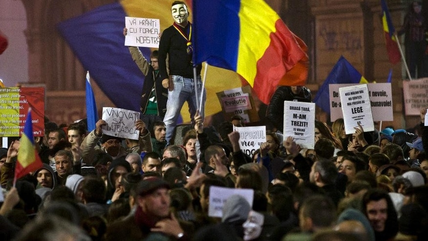 "A man wearing a Guy Fawkes mask stands above protesters shouting slogans against the Romanian politicians during the fourth day of protests, joined by tens of thousands across the country, calling for early elections, in Bucharest, Romania, Friday, Nov. 6, 2015.  Large street protests followed the Oct. 30 nightclub fire, which many Romanians blame on a weak enforcement of regulations and corruption. The street protesters have condemned the nation's politicians as arrogant and corrupt and isolated from the problems of ordinary people. Banners read"" You are feeding on our hunger,"" top left, and ""The culprits must pay,"" bottom left. (AP Photo/Vadim Ghirda)"