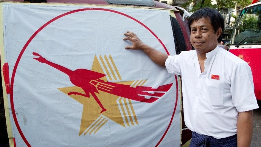 In this Friday, Nov. 6, 2015 photo, Zay Ta, chairman of the New Society Party, stands by his party's symbol, four stars and a peacock in Yangon, Myanmar. Nine of the political parties contesting the country's historic election on Sunday Nov. 8 are using the peacock as their logo, with most bearing a striking resemblance to that of the party headed by pro-democracy leader Aung San Suu Kyi.   (AP Photo/Mark Baker)