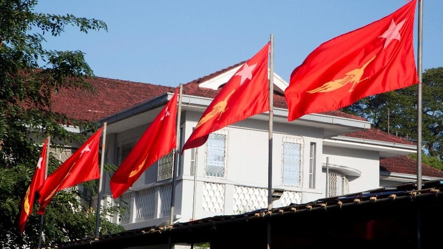 In this Nov. 5, 2015 photo, flags of the National League for Democracy party fly at the home of their leader Aung San Suu Kyi in Yangon, Myanmar. Nine of the political parties contesting the country's historic election are using the peacock as their logo, with most bearing a striking resemblance to that of the party headed by pro-democracy leader Aung San Suu Kyi.  (AP Photo/Mark Baker)