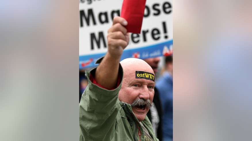 "A man holds a red card during a protest rally of the German party 'Alternative fuer Deutschland, AfD' (Alternative for Germany) in Berlin, Germany, Saturday, Nov. 7, 2015. Text on the sticker reads 'east rage', text on the poster in the background reads 'exorbitant misery'.  The  anti-immigration party has staged a march in Berlin against the German government's migrant policies, with demonstrators chanting ""Merkel must go"" and counter-protesters shouting ""Nazis out.""    (AP Photo/Michael Sohn)"