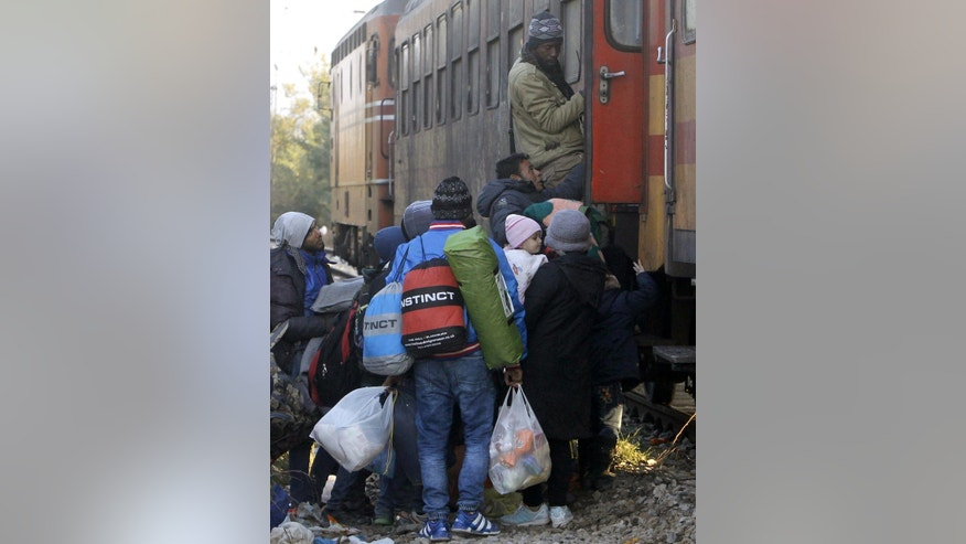 People rush to secure a place onboard a train heading towards Serbia at the transit center for refugees near the southern Macedonian town of Gevgelija, on Saturday, Nov. 7, 2015. Thousands of refugees and migrants are heading to Macedonia from Greece on their way to more prosperous European Union countries, after the Greek seamen's union called off rolling 48-hour ferry strikes that had stranded an estimated 25,000 people on the eastern Aegean islands. (AP Photo/Boris Grdanoski)