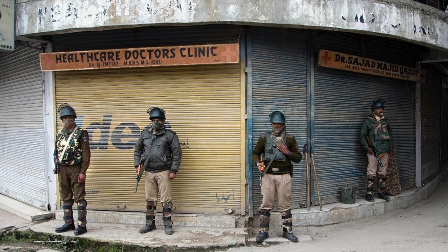 Indian paramilitary soldiers stand guard at a closed market area during restrictions in Srinagar, Indian controlled Kashmir, Saturday, Nov. 7, 2015. Thousands of government forces have fanned out across the Indian portion of Kashmir to provide a security shield for Prime Minister Narendra Modi, who is scheduled to inaugurate a power project and offer a financial aid package a year after the region was devastated by massive floods. (AP Photo/Dar Yasin)