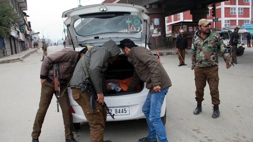 Indian policemen check a vehicle at a temporary checkpoint during restrictions in Srinagar, Indian controlled Kashmir, Saturday, Nov. 7, 2015. Thousands of government forces have fanned out across the Indian portion of Kashmir to provide a security shield for Prime Minister Narendra Modi, who is scheduled to inaugurate a power project and offer a financial aid package a year after the region was devastated by massive floods. (AP Photo/Dar Yasin)