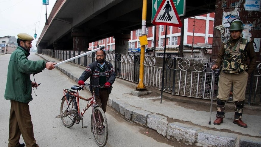 An Indian policeman prevents a Kashmiri cyclist from moving forward at a temporary checkpoint during restrictions in Srinagar, Indian controlled Kashmir, Saturday, Nov. 7, 2015. Thousands of government forces have fanned out across the Indian portion of Kashmir to provide a security shield for Prime Minister Narendra Modi, who is scheduled to inaugurate a power project and offer a financial aid package a year after the region was devastated by massive floods. (AP Photo/Dar Yasin)