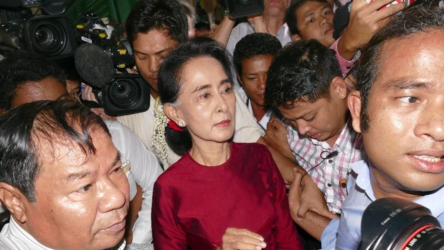Myanmar opposition leader Aung San Suu Kyi, center, leaves after casting her ballot at a polling station in general election Sunday, Nov 8, 2015, in Yangon, Myanmar. Myanmar voted Sunday in historic elections that will test whether popular mandate can loosen the military's longstanding grip on power, even if opposition leader Suu Kyi's party secures a widely-expected victory. (AP Photo/Khin Maung Win)