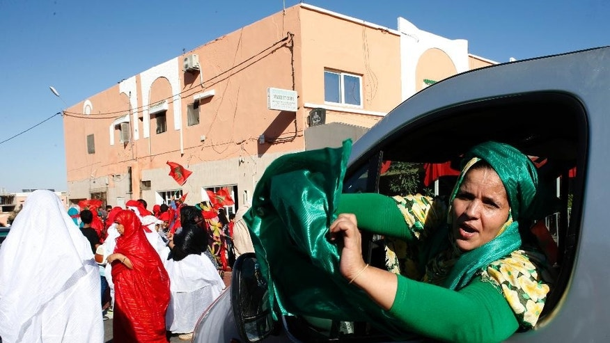 Moroccan women parade in a street of Laayoune, the capital of disputed territories of the Western Sahara, Friday, Nov.6, 2015. Morocco's King Mohammed VI visits the Western Sahara Friday to mark the 40th anniversary of the Green March, when thousands of unarmed Moroccans were sent by his father, late King Hassan II, to pressure Spanish army to withdraw from the territory. (AP Photo/Abdeljalil Bounhar)