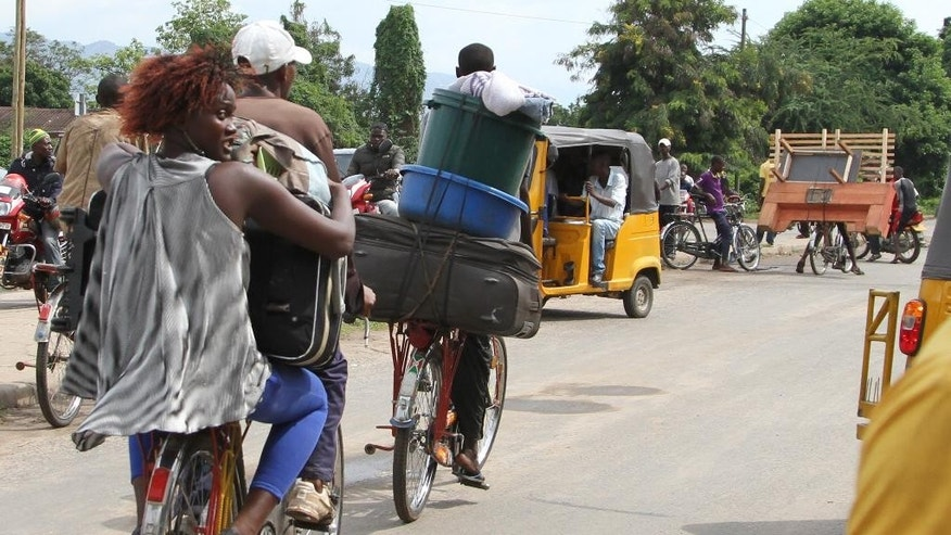Burundians carry their belongings on bicycles in Bujumbura, Burundi, Saturday, Nov. 7, 2015. Carrying their prized possessions, scores of people fled Burundi's capital Saturday before a looming security crackdown that has left many predicting more bloody violence ahead.   (AP Photo)