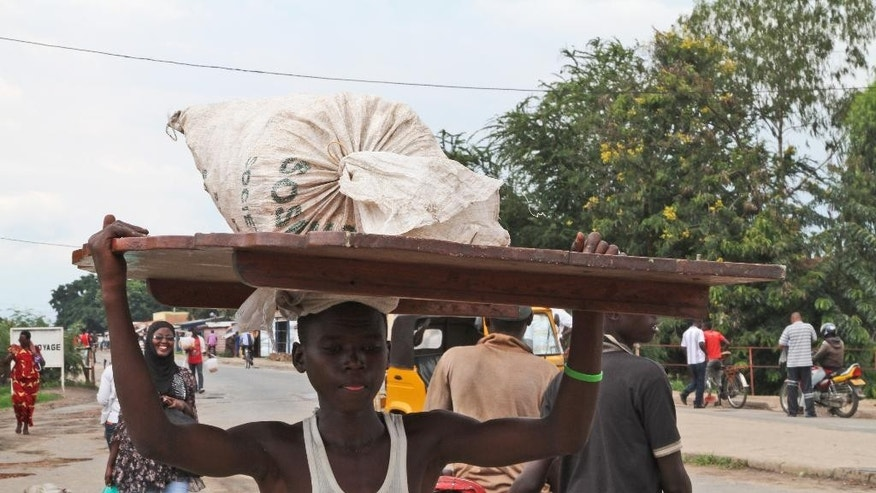 A Burundian man carries his belongings on his head,  in Bujumbura, Burundi, Saturday, Nov. 7, 2015. Carrying their prized possessions, scores of people fled Burundi's capital Saturday before a looming security crackdown that has left many predicting more bloody violence ahead.  (AP Photo)