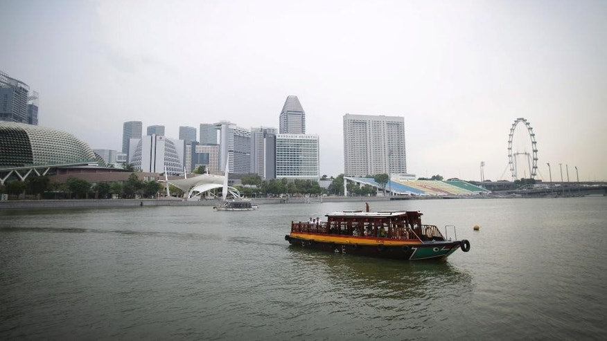In this Thursday, Nov. 5, 2015, photo, a tourist water taxi motors along the Singapore river which runs through the financial district of Singapore. On Saturday, the top officials of both sides,  Chinese President Xi Jinping and his Taiwanese counterpart, Ma Ying-jeou, flew to Singapore to sit down together, the first time that has happened since the Chinese civil war. (AP Photo/Wong Maye-E)