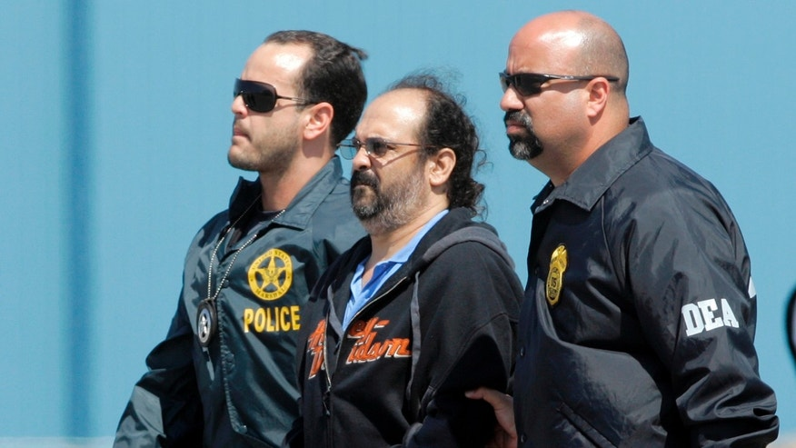 "FILE - In this May 13, 2008 file photo, Colombian paramilitary Rodrigo Tovar Pupo is escorted in handcuffs by U.S. DEA Agents as he arrives to Opa-locka, Florida. A U.S. judge on Friday, Oct. 6, 2015 sentenced the former Colombian paramilitary leader, alias ""Jorge 40"", to just over 16 years in prison for conspiring to import tons of cocaine to the U.S. (AP Photo/Alan Diaz, File)"