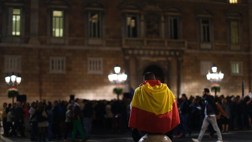 "A man wraps with a Spanish flag during a demonstration calling for the ""unity of Spain"" in Barcelona, Spain, Thursday, Nov. 5, 2015. Three anti-independence parties filed complaints Wednesday before Spain's Constitutional Court against moves by the regional parliament of Catalonia to announce the formal start of independence from Spain. (AP Photo/Manu Fernandez)"