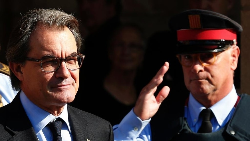 Regional acting president Artur Mas leaves parliament in Barcelona, Spain, Monday, Nov. 9, 2015. The regional parliament of northeastern Catalonia is due to vote on a proposal by secessionist parties that hold a majority in the chamber to set up a road map for independence from Spain by 2017. The initiative defies Spain's central government, which considers it unconstitutional. (AP Photo/Manu Fernandez)
