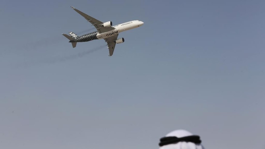 An Emirati man watches as an Airbus A350 XWB performs during the opening of the Dubai Airshow in Dubai, United Arab Emirates, Sunday, Nov. 8, 2015. (AP Photo/Kamran Jebreili)