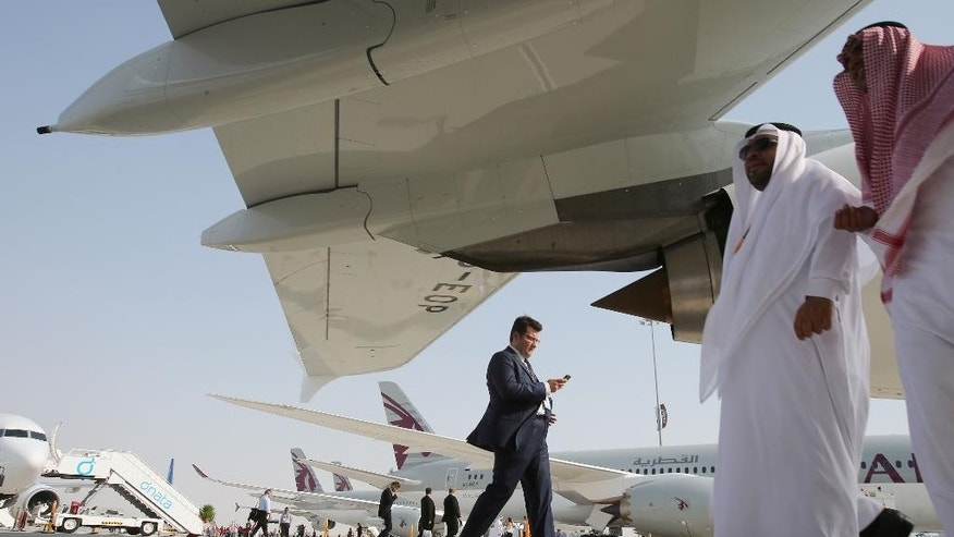 People walk around the planes during the opening of the Dubai Airshow in Dubai, United Arab Emirates, Sunday, Nov. 8, 2015. (AP Photo/Kamran Jebreili)