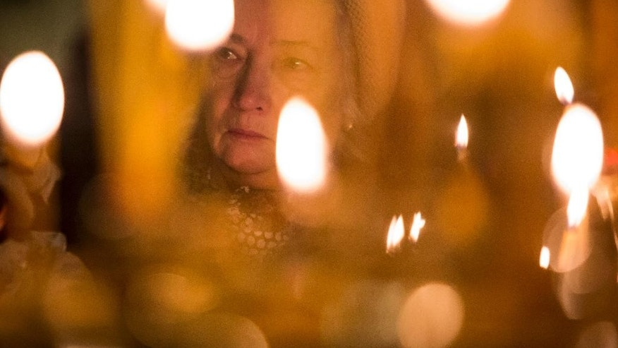 A woman takes part in a memorial religious service for plane crash victims at the St.Isaac's Cathedral in St.Petersburg, Russia, Sunday, Nov. 8, 2015.  Mourners have packed into the landmark St. Isaac's Cathedral in St. Petersburg for a memorial service for victims of the Russian plane crash, and as a choir sang, the bell of the world's fourth-largest cathedral was tolling once for each of the 224 victims. Most of the victims were from St. Petersburg or other areas of northwest Russia. (AP Photo/Elena Ignatyeva)