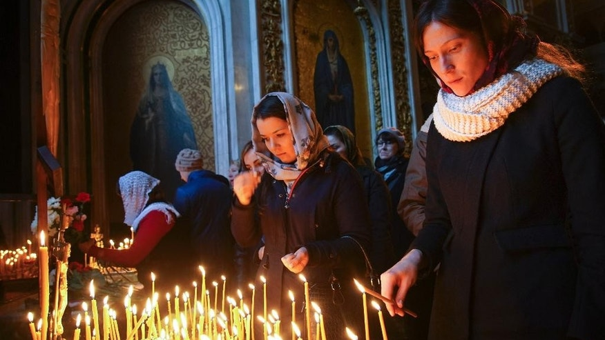 People light candles during a memorial religious service for plane crash victims at the St.Isaac's Cathedral in St.Petersburg, Russia, Sunday, Nov. 8, 2015. Mourners have packed into the landmark St. Isaac's Cathedral in St. Petersburg for a memorial service for victims of the Russian plane crash, and as a choir sang, the bell of the world's fourth-largest cathedral was tolling once for each of the 224 victims. Most of the victims were from St. Petersburg or other areas of northwest Russia. (AP Photo/Mstyslav Chernov)