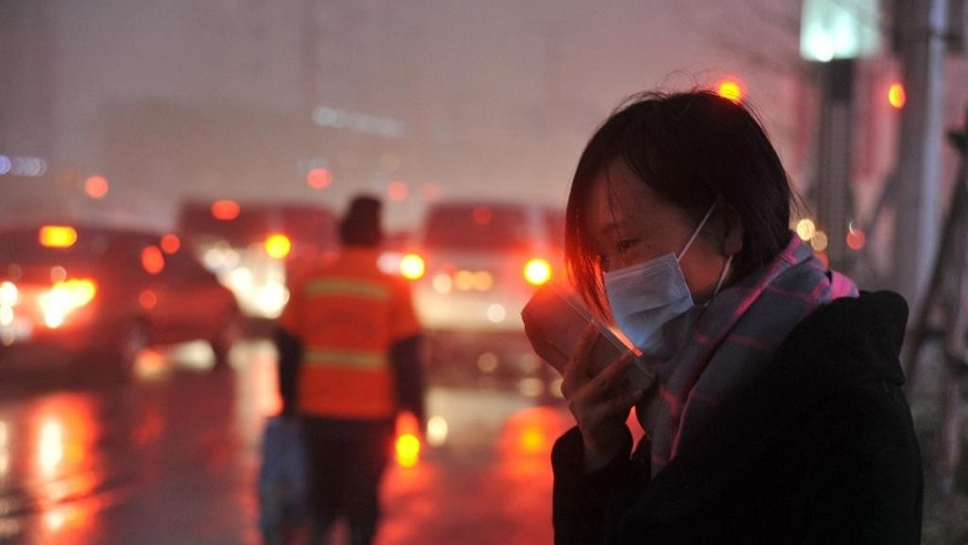 A woman wearing a face mask checks her mobile phone amid a heavy haze in Shenyang in northeastern China's Liaoning province Sunday, Nov. 8, 2015. Air quality reached extremely hazardous levels in the northeastern city of Shenyang on Sunday, as northern China began to burn coal to heat homes for winter. (Chinatopix via AP) CHINA OUT