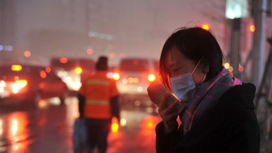 Nov. 8, 2015: A woman wearing a face mask checks her mobile phone amid a heavy haze in Shenyang in northeastern China's Liaoning province.