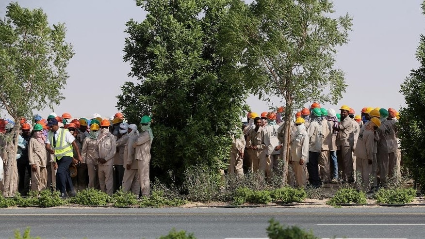 Migrant laborers walk during a protest near the airport hosting the biennial Dubai Airshow in the United Arab Emirates, Sunday, Nov. 8, 2015. Hundreds of migrant laborers have staged a protest near the airport hosting the biennial Dubai Airshow. Associated Press journalists saw the workers gathering and shouting along a road leading to the Dubai World Central airport, the Gulf city's second airport. (AP Photo/Kamran Jebreili)