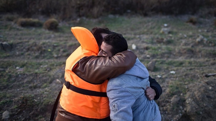 Two men embrace after they had disembarked a small boat at a beach on the island of Lesbos, Greece, Sunday, Nov. 8, 2015. Well over half a million people have reached the Greek islands so far this year, a record number of arrivals, and the journey has proved fatal for hundreds. (AP Photo/Marko Drobnjakovic)