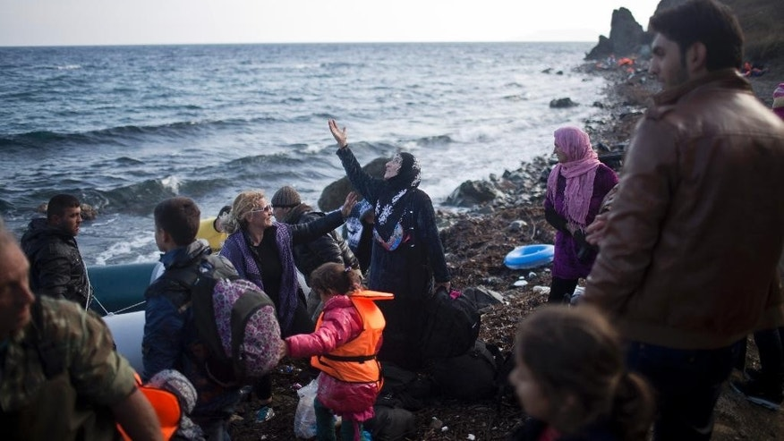 A woman gestures as she had just disembarked a small boat at a beach on the island of Lesbos, Greece, Sunday, Nov. 8, 2015. Well over half a million people have reached the Greek islands so far this year, a record number of arrivals, and the journey has proved fatal for some hundreds. (AP Photo/Marko Drobnjakovic)