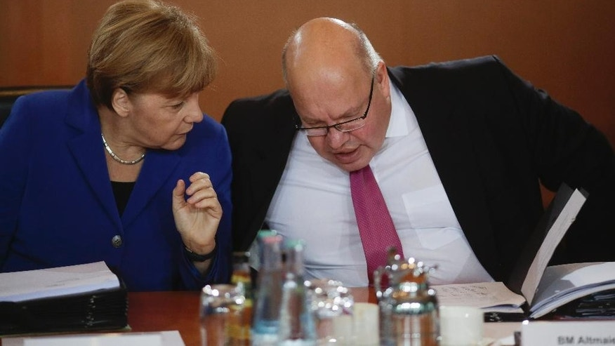 FILE - In this Oct. 7, 2015 file picture German Chancellor Angela Merkel, left, talks to the Chief of Staff Peter Altmaier  in Berlin.Peter Altmaier is downplaying a short-lived initiative by the interior minister Thomas de Maiziere to give many Syrians restricted asylum, insisting that the matter is settled and procedures remain unchanged. Altmaier, made clear in an interview with Deutschlandfunk radio broadcast Sunday Nov. 8, 2015  that he hadn't been aware that the initiative had been launched.  (AP Photo/Markus Schreiber,file)