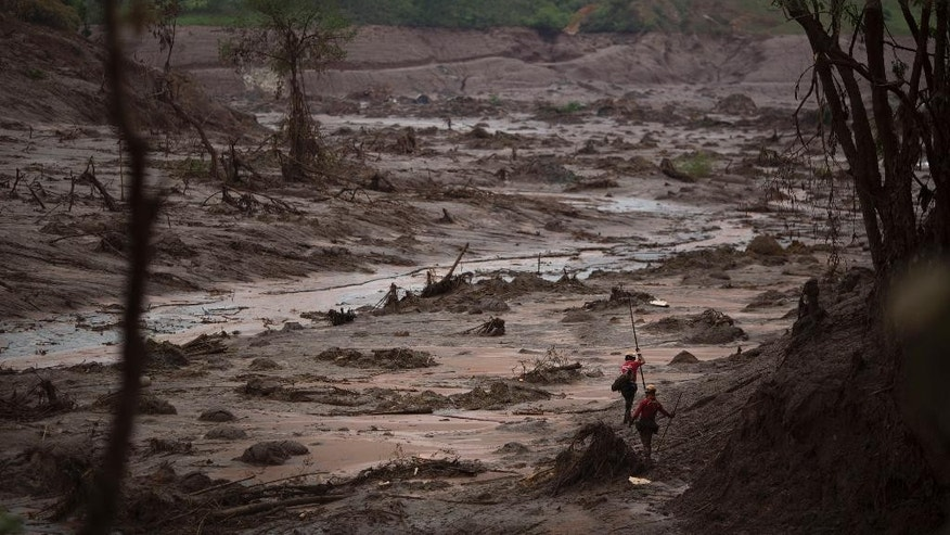 Rescue workers search for victims at the site where the town of Bento Rodrigues stood, after two dams burst on Thursday, in Minas Gerais state, Brazil, Sunday, Nov. 8, 2015. Brazilian rescuers are looking for people still listed as missing following the burst of two dams at an iron ore mine which sent viscous red mud, water and debris flooding into the town, flattening all but a handful of buildings and killing dozens. (AP Photo/Felipe Dana)