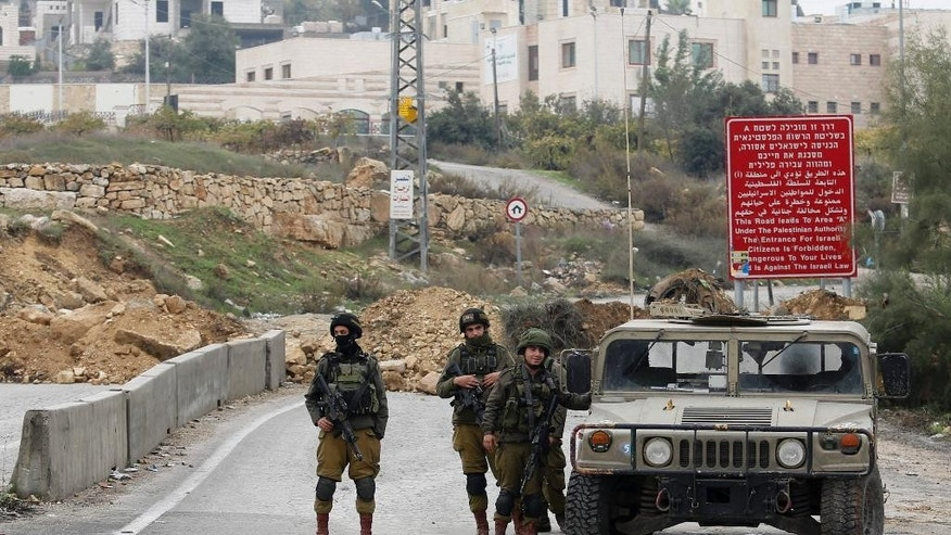 Israeli soldiers stand guard after the military blocked the road with an earth berm at one of the exits of the West Bank city of Hebron, Saturday, Nov. 7, 2015. Three incidents took place Friday in Hebron, the West Bank's largest city, which has been the main area of friction in recent weeks. Hundreds of combat troops guard about 850 Jewish settlers in the center of Hebron where they live amid tens of thousands of Palestinians. (AP Photo/Nasser Shiyoukhi)