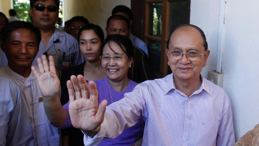 Myanmar's President Thein Sein, right, waves after casting his vote in Naypyitaw, Myanmar, Sunday, Nov. 8, 2015. Myanmar voted Sunday in historic elections that will test whether popular mandate will help loosen the military's longstanding hold on power even if opposition leader Aung San Suu Kyi's party secures a widely-expected victory. (AP Photo/Aung Shine Oo)