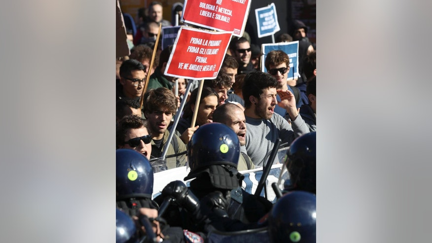 "Protesters hold signs with writing in Italian reading, from top, ""Bologna is half-caste, free, and supportive! First Padania? First Italians? First you leave the better!"" as they march and shout slogans, in Bologna, Italy, Sunday, Nov. 8, 2015. Hundreds of demonstrators gathered in Bologna to protest the arrival of Northern League leader Matteo Salvini, whom they decried as a racist for his anti-migrant views, and his meeting with former premier Silvio Berlusconi. The demonstrators clashed briefly with police. (Giorgio Benvenuti/AP via ANSA) ITALY OUT"