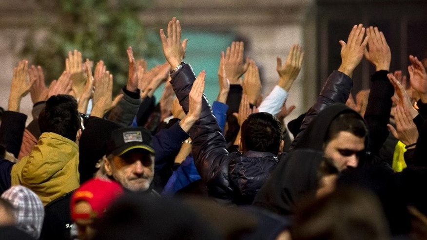 People raise their hands shouting slogans against politicians during the fifth day of protests in Bucharest, Romania, Saturday, Nov. 7, 2015,  calling for better governance and an end to corruption, in Bucharest, Romania, Nine more people died Saturday, bringing the death toll to 41 victims, a week after the Oct. 30 blaze that erupted at the Colectiv nightclub during a heavy-metal concert. (AP Photo/Vadim Ghirda)