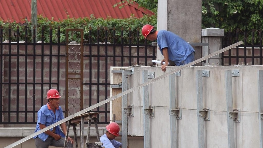 FILE - In this file photo dated May 20, 2015, Chinese workers at the building site of a new hotel to be used by Congo government officials when completed in Kinshasa, Democratic Republic of Congo.  Climate change could push more than 100 million people into extreme poverty by 2030 by disrupting agriculture and fueling the spread of malaria and other diseases, the World Bank said in a report Sunday Nov. 8, 2015, which also stated Carbon emissions are expected to rise for many years as China, India and other developing countries expand the use of fossil fuels to power their economies. (AP Photo/John Bompengo, FILE)
