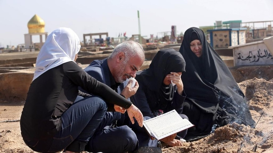 In this Sunday, Nov. 8, 2015 photo, Mohammed al-Qurayshi and his family members pray around the graves of two daughters  Fatima, 14, and Rosul, 15,  killed when they were electrocuted during flooding, at the cemetery in Najaf, 100 miles (160 kilometers) south of Baghdad, Iraq. The Iraqi Ministry of Health said 69 people have died across the country over the past two weeks, due to a combination of the country's dilapidated electrical grid and heavy rains that overwhelmed sewer systems. (AP Photo/Hadi Mizban)
