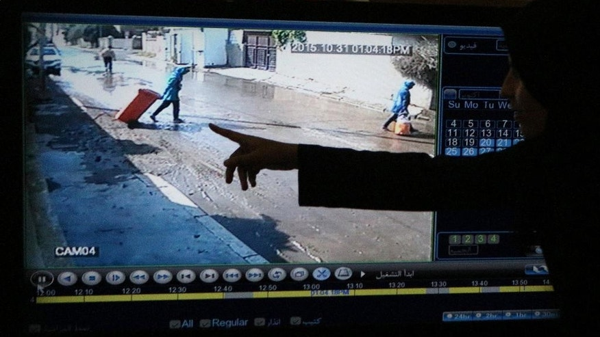 In this Saturday, Nov. 7, 2015 photo, a relative points at CCTV footage of Fatima Mohammed, left and her sister Rosul before their death by electric shock outside their house in Baghdad. Iraqi. Iraqi Ministry of Health said 69 people have died across the country over the past two weeks, due to a combination of the country's dilapidated electrical grid and heavy rains that overwhelmed sewer systems. (AP Photo/Hadi Mizban)