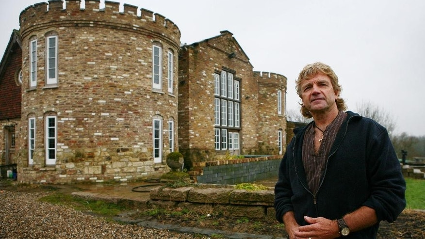 FILE - In this Feb. 3, 2010 file photo, farmer Robert Fidler stands outside the mock Tudor castle home at Honeycrock Farm, Salfords, England. A judge ruled Monday Nov. 9, 2015 that the 66-year-old farmer will go to prison if he doesn't demolish a mock-Tudor castle he built without planning permission. (Gareth Fuller/PA via AP, File) UNITED KINGDOM OUT