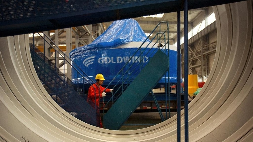 A worker pushes a portable staircase past a wind turbine power generator at a factory in Beijing, Monday, Nov. 9, 2015. Heading into this month's Paris climate meeting, China, the world's biggest source of climate-changing gases, has yet to accept binding limits. But it has invested in solar, wind and hydro power to clean up its smog-choked cities and curb surging demand for imported oil and gas. (AP Photo/Mark Schiefelbein)
