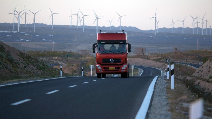 In this photo taken Friday, Oct. 9, 2015, a truck travels down a highway with wind turbines in the background in northwestern China's Ningxia Hui autonomous region. Heading into this month's Paris meeting, the world's biggest source of climate-changing gases has yet to accept binding limits. But it has invested in solar, wind and hydro power to clean up its smog-choked cities and curb surging demand for imported oil and gas. That contributed last year to a surprise fall in coal consumption. (AP Photo/Ng Han Guan)