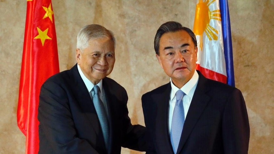 Chinese Foreign Minster Wang Yi, right, is greeted by Philippine Foreign Secretary Albert Del Rosario upon arrival at the Department of Foreign Affairs Tuesday, Nov. 10, 2015 at suburban Pasay city, south of Manila, Philippines. It was Wang's first visit to the country amid the two countries' row over the Spratlys group of islands in the South China Sea.(AP Photo/Bullit Marquez)