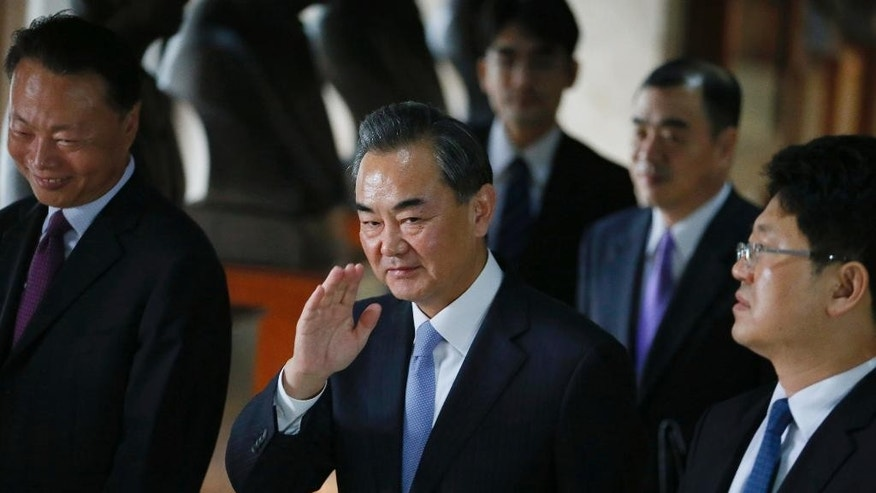 Chinese Foreign Minster Wang Yi, center, waves to the media as he leaves the Department of Foreign Affairs following his talks with Philippine Foreign Secretary Albert Del Rosario Tuesday, Nov. 10, 2015 at suburban Pasay city, south of Manila, Philippines. It was Wang's first visit to the country amid the two countries' row over the Spratlys group of islands in the South China Sea. (AP Photo/Bullit Marquez)