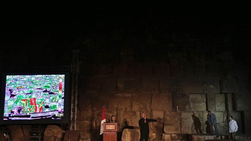 French architect Jean-Pierre Houdin, right, and Egypt's Antiquities Minister Mamdouh el-Damaty, second right, stand near the limestone rocks that are displayed on the screen showing varying temperatures represented by different colors with live footage from a thermal camera, in front of the Khufu pyramid in Giza, Egypt, Monday, Nov. 9, 2015. Egypt's Antiquities Ministry says a scanning project in the Giza pyramids has identified thermal anomalies, including one in the largest pyramid, built by Cheops, known locally as Khufu. (AP Photo/Nariman El-Mofty)