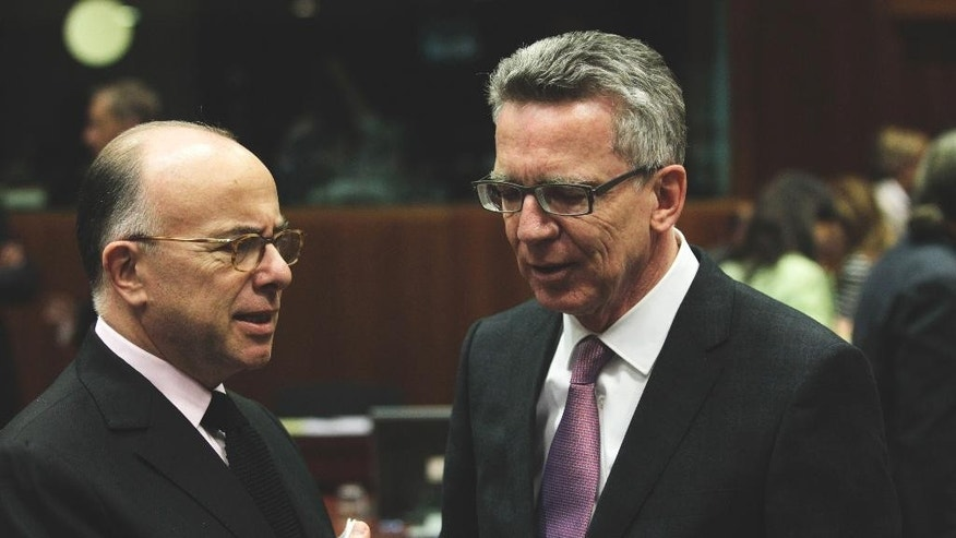 French Interior Minister Bernard Cazeneuve, left, speaks with German Interior Minister Thomas de Maiziere during a round table meeting of EU justice and interior ministers at the EU Council building in Brussels on Monday, Nov. 9, 2015. EU justice and interior ministers met Monday to discuss the ongoing crisis of migrants and refugees. (AP Photo/Francois Walschaerts)